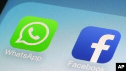 FILE - This Feb. 19, 2014, file photo, shows WhatsApp and Facebook app icons on a smartphone in New York. Global messaging service WhatsApp says it will start sharing the phone numbers of its users with Facebook, its parent company.