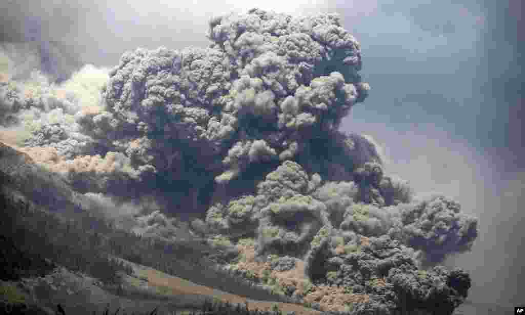 Mount Sinabung releases pyroclastic flows during an eruption as seen from Payung village, North Sumatra, Indonesia. The rumbling volcano unleashed fresh clouds of searing gas, killing more than a dozen people.