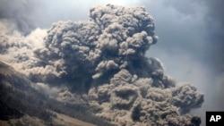 Gunung Sinabung melepaskan uap panas, terlihat dari desa Payung, Sumatera Utara (3/2). (AP/Binsar Bakkara)