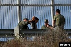 이민세관단속국(ICE)' 요원이 지난 18일 미 국경을 불법으로 넘은 이민자를 체포하고 있다.