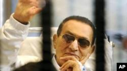 埃及前总统穆巴拉克在一次庭审中向支持者挥手致意(资料照片)