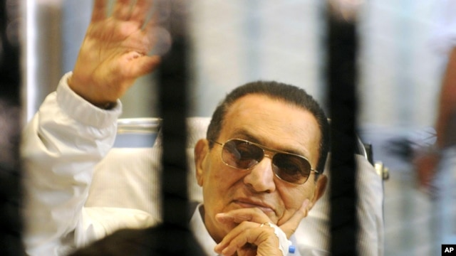 Former Egyptian President Hosni Mubarak waves to his supporters from behind bars as he attends a hearing in his retrial on appeal in Cairo, Egypt.  (File photo)