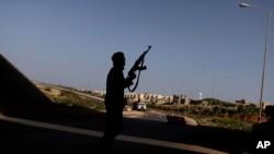 Un rebelle libyen sécurise un poste de contrôle à Benghazi, Libye, le 30 mars 2011.