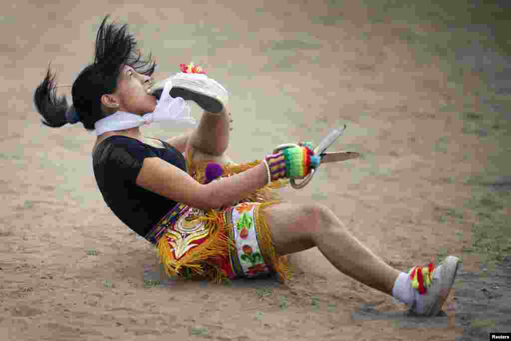 """A """"scissors"""" dancer grabs her shoe with her mouth while performing in a national scissors dance competition in the outskirts of Lima, Peru, Dec. 1, 2013."""