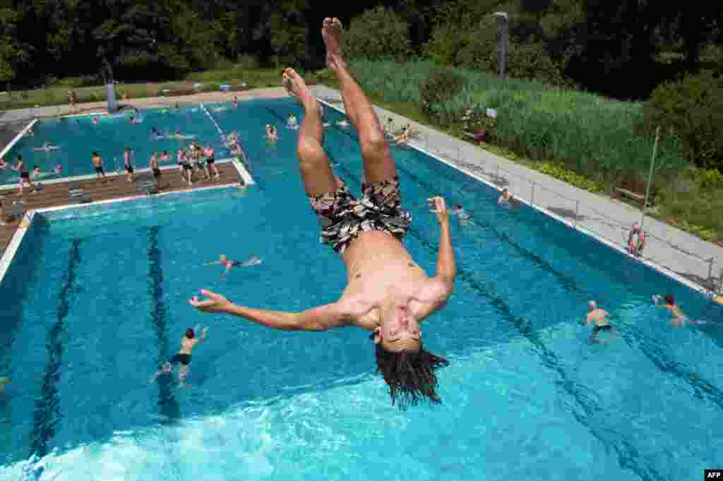 Leopold jumps into the water of the Freibad Wostra public open air pool in Dresden, eastern Germany.