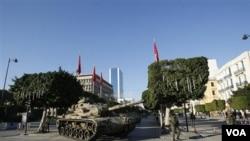 Sebuah tank dan sejumlah tentara melakukan patroli di pusat ibukota Tunis, 16 Januari 2011.