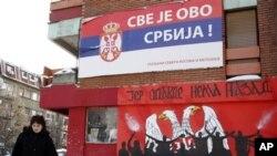 Seorang warga melewati bangunan berbendera Serbia dengan slogan 'Semuanya Milik Serbia' di kota Mitrovica, Kosovo (Foto: dok). Pertikaian antar etnis terus berlangsung di kota itu.
