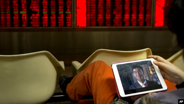 A Chinese investor watches a video on a tablet computer while monitoring stock prices in a brokerage house in Beijing, Jan. 29, 2016.