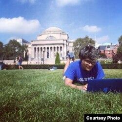 컬럼비아 대학교 교정 잔디밭에 엎드려 노트북을 사용하는 학생.