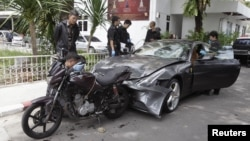 FILE - Policemen examine a damaged Ferrari at the home of the late Red Bull founder Chaleo Yoovidhaya in Bangkok, Sept. 3, 2012.The grandson of the owner of Red Bull — the famous energy drink from Thailand — has been linked to the hit-and-run death of a police officer.