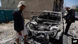 Men look at a car destroyed by a recent Saudi-led airstrike in Yemen's capital, Sana'a, April 25, 2015.