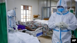FILE - In this Aug. 20, 2021 photo, medical workers prepare to remove the body of a coronavirus victim in the intensive care unit of a hospital in Machakos, Kenya.