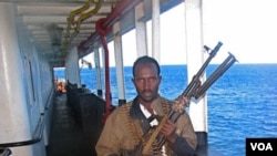 Anggota bajak laut Somalia dengan senjatanya. Uang yang dibawa pesawat asing diduga 'uang tebusan' bagi bajak laut Somalia.