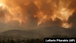 FILE - In this Friday, Aug. 6, 2021 file photo, smoke spreads over Parnitha mountain during a wildfire in the village of Ippokratios Politia, Greece, about 35 kilometres (21 miles), north of Athens. (AP Photo/Lefteris Pitarakis)