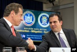 Gov. Andrew Cuomo, left, and Puerto Rico Gov. Ricardo Rossello shake hands at a news conference, Nov. 2, 2017, in New York. Cuomo announced that the state will be sending personnel and trucks to aid in the reconstruction of Puerto Rico's electrical grid.