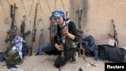 A Kurdish female fighter from Kurdish People's Protection Units [YPG] checks her weapon near Ras al-Ain, in the province of Hasakah, after capturing it from Islamist rebels, November 6, 2013.