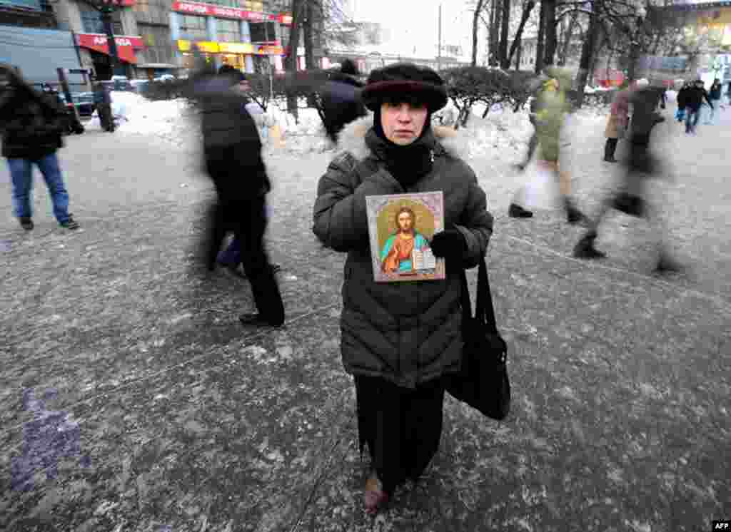 A woman holds a religious icon as she takes part in a rally to commemorate the victims of a bomb explosion at Domodedovo airport in central Moscow. (Reuters/Nikolay Korchekov)