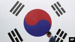 Seorang pria berjalan dengan bendera nasional besar yang dicetak di dinding di Seoul, Korea Selatan, Rabu, 26 Oktober 2016. (Foto: AP/Lee Jin-man)