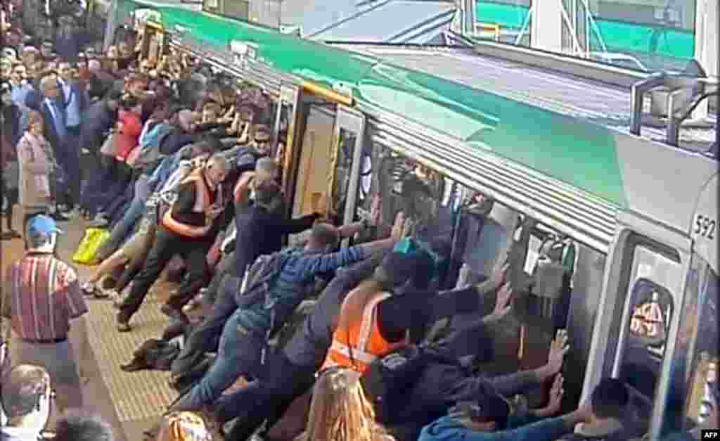 A video frame grab from the Public Transport Authority of Western Australia shows commuters pushing a train to free a passenger in Perth.  The passenger's leg was trapped between the train and the gap along the track.