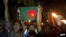 Former Indian enclave residents carry torches and a Bangladesh flag as they celebrate at Dasiarchhara, Kurigram in Bangladesh, as Bangladesh and India swapped tiny islands of land, ending one of the world's most intractable border disputes, Aug. 1, 2015.