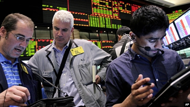 Traders work in the crude oil and natural gas options pit at the New York Mercantile Exchange in New York, (File June 29, 2011).