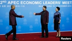 U.S. President Barack Obama (L) shakes hands with China's President Xi Jinping as Xi's wife, Peng Liyuan, looks on, during the APEC Welcome Banquet in Beijing, Nov. 10, 2014.