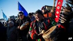 FILE - Dan Nanamkin of the Colville Nez Perce Native American tribe in Nespelem, Washington, right, drums with a procession through the Oceti Sakowin camp in Cannon Ball, North Dakota, Dec. 4, 2016.