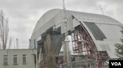 FILE - A new sarcophagus (shown under construction in 2014), the world's largest movable object, is to be placed over the Chernobyl plant in 2017, March 20, 2014. (S. Herman/VOA)