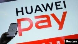 華為公司一名工作人員在2019年1月24日北京舉行的華為5G產品發佈會上顯示其手機支付系統。