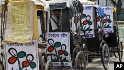 A man sits in a trishaw decorated with Trinamool Congress (TMC) placards on a roadside in Kolkata. Voters streamed into polling stations in West Bengal on Monday in state elections that could see populist maverick Mamata Banerjee unseat the world's longes
