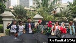 Aktivis Aliansi Remaja Independen (ARI) Aditya Septiansyah (ketiga kiri) berpose di depan Kementerian Pemberdayaan Perempuan dan Perlindungan Anak yang dilewati rute pawai, Jakarta, Sabtu, 8 Desember 2018. (Foto: Rio Tuasikal/VOA)