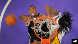 Jason Collins memperkuat tim Brooklyn Nets (kiri) berhadapan dengan Jordan Hill dari tim basket Los Angeles Lakers di Los Angeles (23/2).