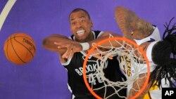 Jason Collins, de los Nets de Brooklyn, intenta recuperar un rebote que buscaba Jordan Hill, de los Lakers, en su debut como jugador abiertamente gay.