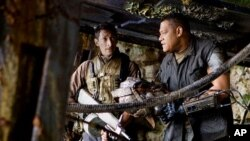 Noland (Laurence Fishburne) right, and Royce (Adrien Brody) reveals some of the secrets of living on an alien world -- amidst alien Predators