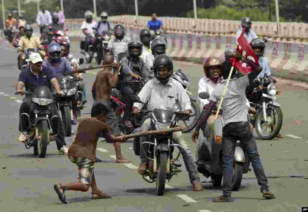 Activists of a trade union group stop motorcyclists to keep vehicles off the road during a daylong nationwide strike in the eastern Indian city Bhubaneswar. Ten central trade unions staged a protest against changes in labor laws and privatisation of Public Sector Undertaking's (PSU) by the ruling Bharatiya Janata Party (BJP) government.