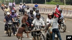 Activists of a trade union group stop motorcyclists to keep vehicles off the road during a daylong nationwide strike in the eastern Indian city Bhubaneswar, India, Wednesday, Sept. 2, 2015.