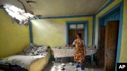 Bir kadın, Ermenistan'a ait güçlerin Azerbaycan'ın Tovuz bölgesine yönelik topçu saldırısından sonra evinde oluşan hasarı gösteriyor.