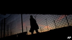 FILE - A migrant is seen walking after crossing a fence as he attempts to access the Channel Tunnel in Calais, northern France. The new controls will be part of larger security measures around the climate conference