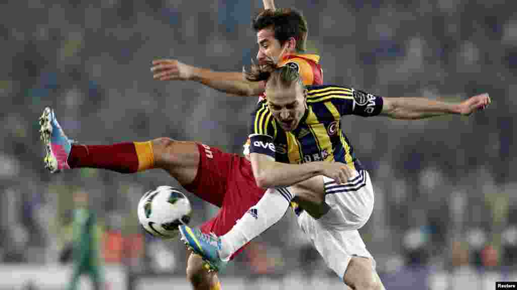 Fenerbahce's Caner Ertekin (R) fights for the ball with Galatasaray's Aydin Yilmaz during their Turkish Super League derby soccer match at Sukru Saracoglu stadium in Istanbul May 12, 2013.