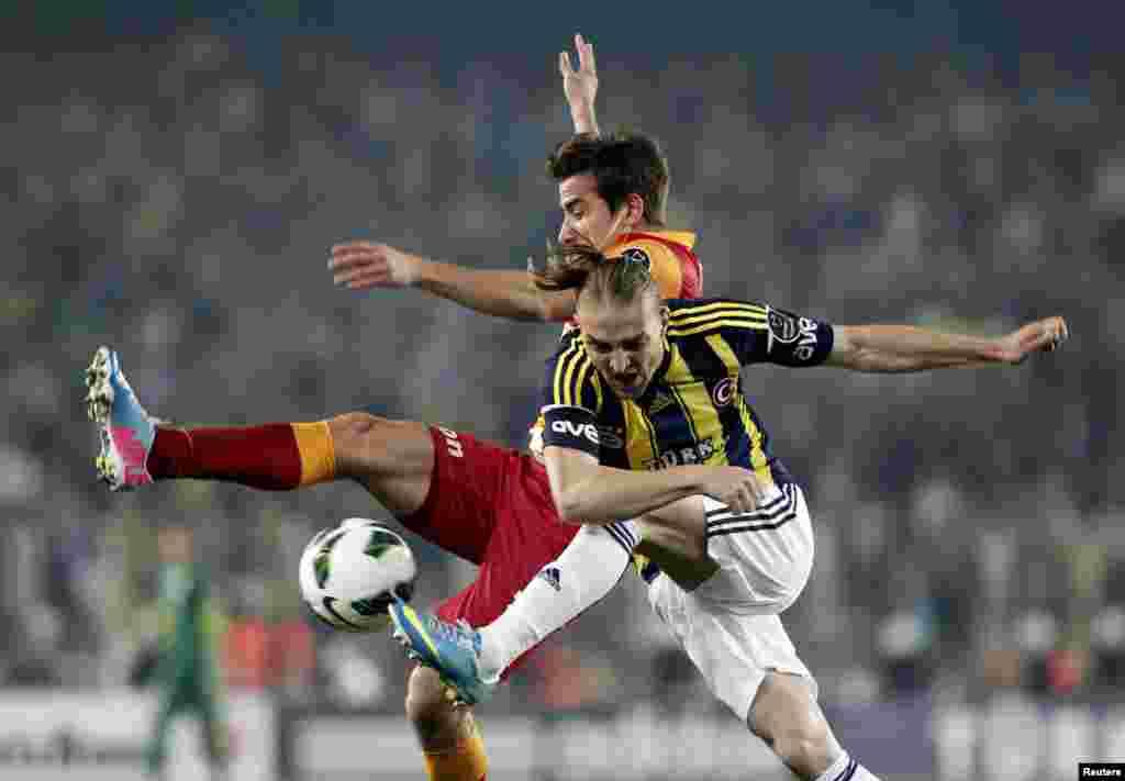 Caner Ertekin (dir.) do Fenerbahce luta pela bola com Aydin Yilmaz do Galatasaray durante o jogo da Super Liga Turca no estádio Sukru Saracoglu em Istambul (12 Maio)