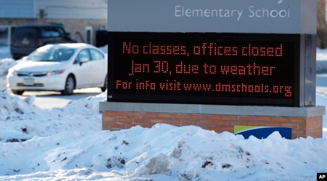 A car passes an elementary school closed due to cold weather in Des Moines, Iowa, Jan. 30, 2019.