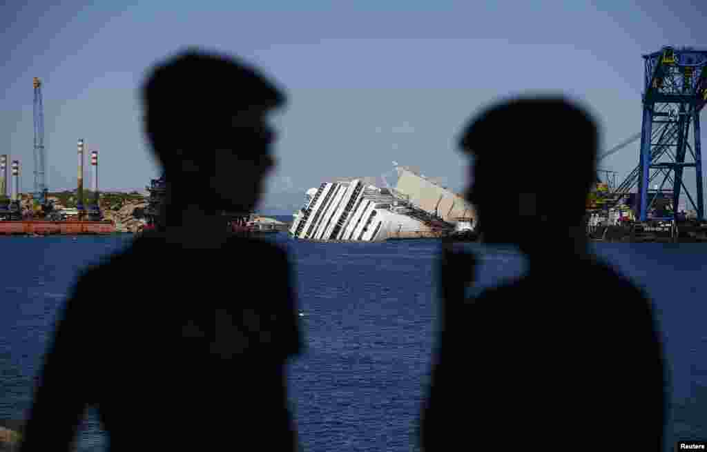 People are silhouetted as the capsized cruise liner Costa Concordia lies surrounded by cranes outside Giglio harbor.