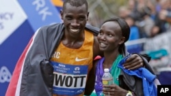 Kenya's Stanley Biwott (L) embraces fellow Kenyan Mary Keitany after the pair won the men's and women's professional athlete divisions in the the New York City marathon, Nov. 1, 2015, in New York.