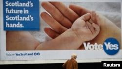 """Un hombre pasa frente a un cartel que lee """"El futuro de Escocia está en manos de Escocia"""", en Aberdeen, Escocia."""