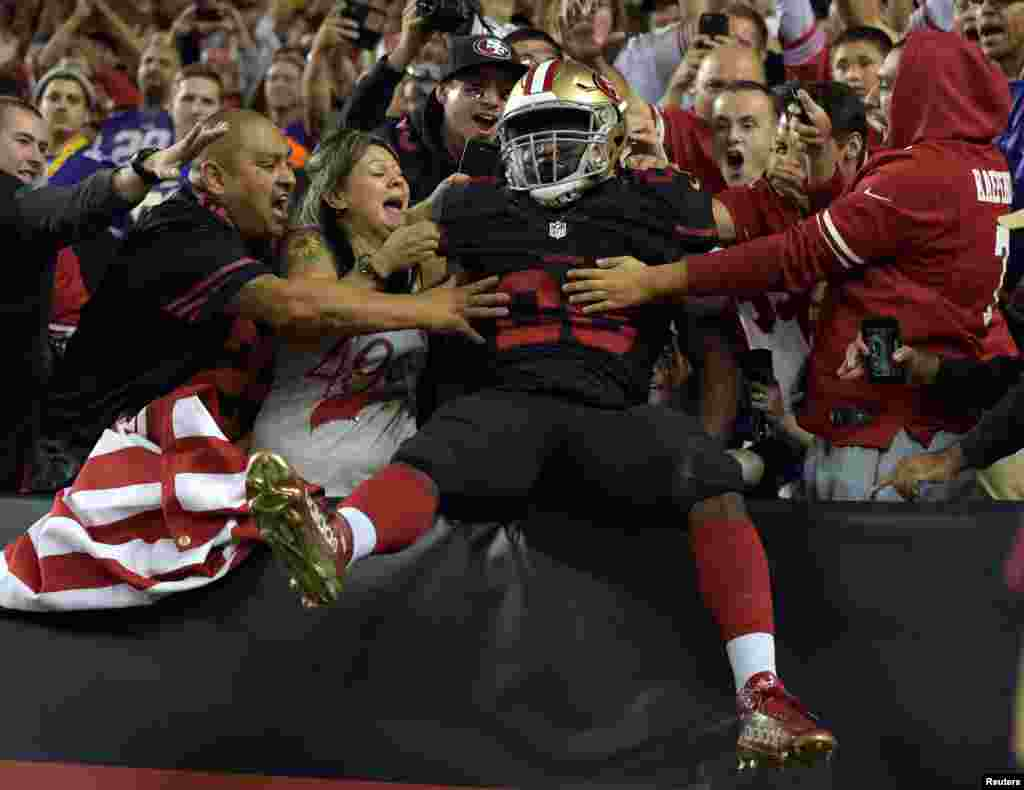 Santa Clara, CA, USA; San Francisco 49ers running back Carlos Hyde (28) celebrates with fans after scoring on a 10-yard touchdown run in the fourth quarter against the Minnesota Vikings at Levi's Stadium, Santa Clara, California, Sept. 14, 2015. (Credit: Kirby Lee-/USA TODAY Sports)