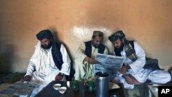 巴基斯坦人在茶館裡閱讀當地報紙關於基地組織資深領導人毛利塔尼被捕的報導