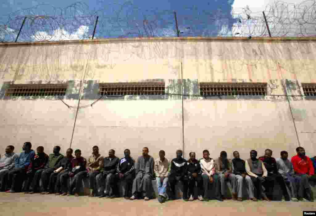 March 24: Mercenaries and forces loyal to Libyan leader Muammar Gaddafi sit inside a prison in Benghazi. (Reuters)