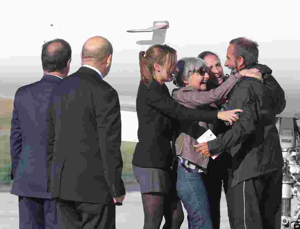 Released French hostage Daniel Larribe, right, is surrounded by his wife and two daughters as President Francois Hollande, left, and Defense Minister Jean-Luc Le Drian, second left, look on after Larribe's arrival at Villacoublay military airbase, outside Paris. Larribe and three other Frenchmen were held hostage in the Sahara desert by al-Qaida-linked gunmen for three years.