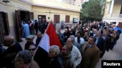 14일 이집트에서 새 헌법 개정안에 대한 국민투표가 시작된 가운데, 카이로의 한 투표소에 유권자들이 줄을 서 있다.