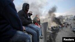 Người biểu tình Palestine ngồi trên bức tường gây tranh cãi của Israel ngăn cách thị trấn Abu Dis ở Bờ Tây với Jerusalem, 17/11/2014.